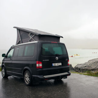 Black VW California camper with the popup roof up at the beach in Flakstad